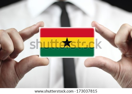 Businessman holding a business card with Ghana Flag - stock photo