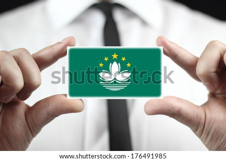 Businessman holding a business card with Macau Flag - stock photo