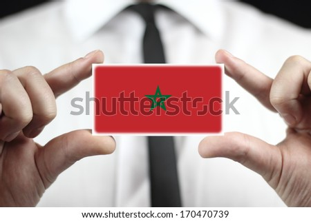 Businessman holding a business card with Morocco Flag - stock photo