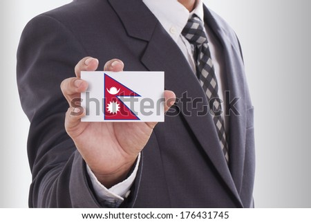 Businessman holding a business card with Nepal Flag  - stock photo