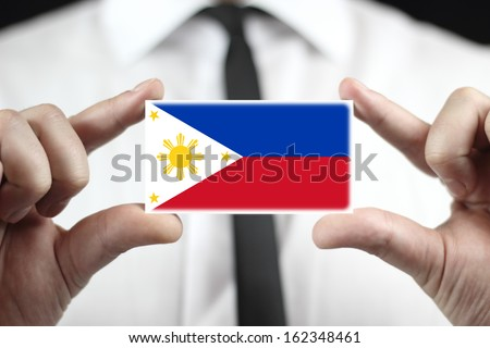 Businessman holding a business card with Philippines Flag - stock photo