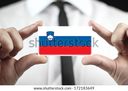 Businessman holding a business card with Slovenia Flag - stock photo