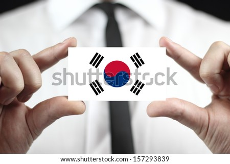 Businessman holding a business card with South Korea Flag - stock photo