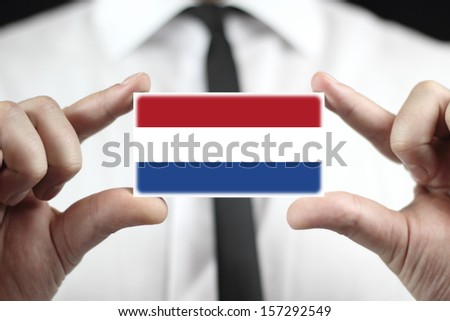 Businessman holding a business card with The Netherlands Flag