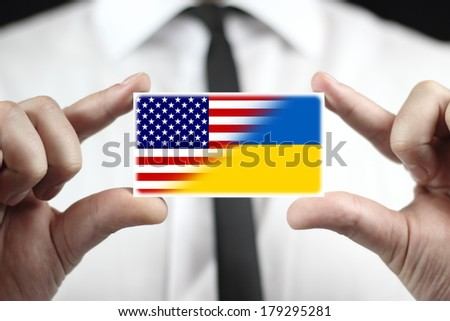 Businessman holding a business card with Ukraine and USA Flag - stock photo