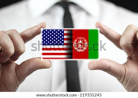 Businessman holding a business card with USA and Afghanistan Flag - stock photo