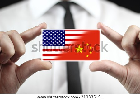 Businessman holding a business card with USA and China Flag