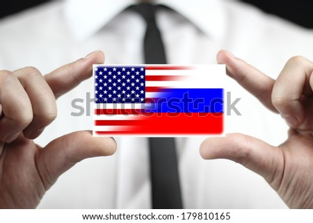 Businessman holding a business card with USA and Russia Flag - stock photo