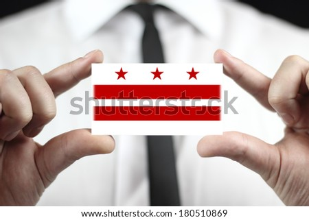 Businessman holding a business card with Washington DC Flag - stock photo