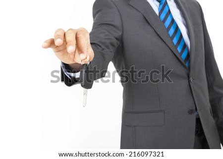 Businessman holding a car key. Isolated over white background