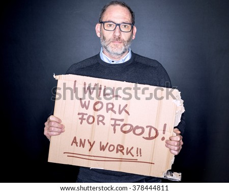 Businessman holding a cardboard sign Looking for a job in his Hands, will work for food - stock photo