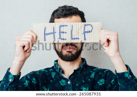 Businessman holding a cardboard with the text Help, isolated on gray background - stock photo