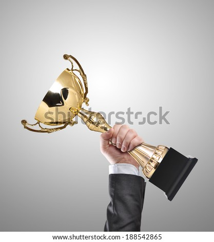 Businessman holding a champion golden trophy - stock photo