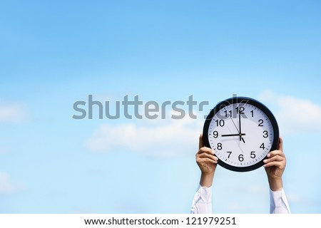 Businessman holding a clock against blue sky,copy space for your text. - stock photo