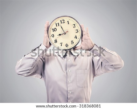 businessman holding a clock on his face