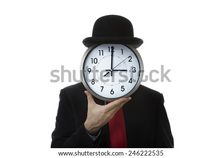 Businessman holding a clock up covering his face wearing a bowler hat - stock photo