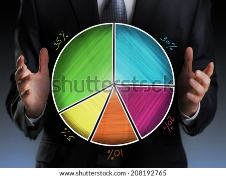 Businessman holding a colorful pie chart - stock photo