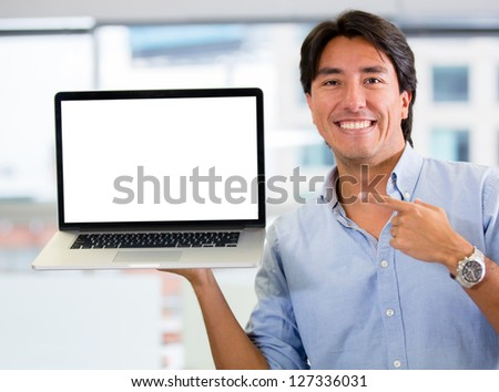 Businessman holding a computer and displaying the screen - stock photo