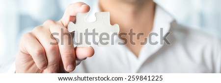 Businessman Holding a Conceptual White Jigsaw Puzzle Piece in Close up Using his Bare Hand. - stock photo
