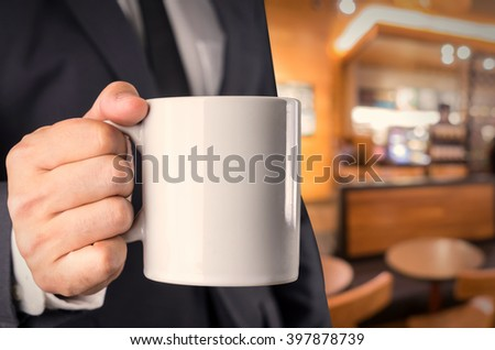 Businessman holding a cup of coffee at cafe in blur background - stock photo