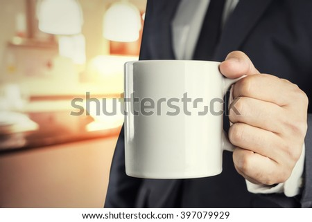 Businessman holding a cup of coffee  with cafe blur background - stock photo