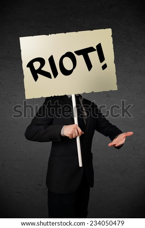 Businessman holding a demonstration board with riot sign in front of his head - stock photo