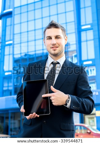 Businessman holding a digital tablet computer, standing in front of his office.