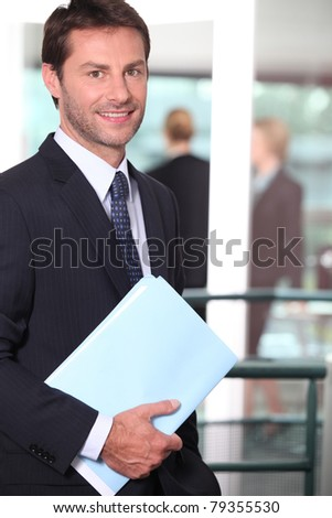 Businessman holding a file with colleagues out of focus in the background - stock photo