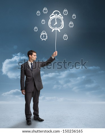 Businessman holding a floating alarm clocks with clouds on the background