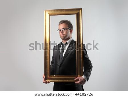 businessman holding a frame - stock photo