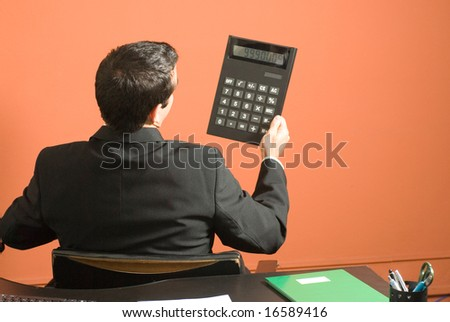 Businessman holding a giant calculator while seated at his desk. Horizontally framed photo - stock photo
