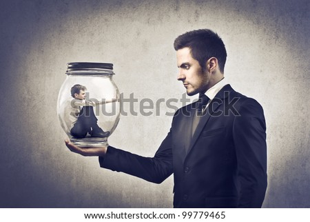 Businessman holding a glass jar with a younger businessman trapped in it - stock photo
