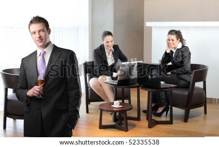 Businessman holding a glass of wine and two smiling businesswomen on th background - stock photo