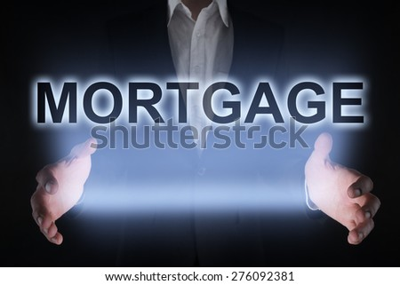 Businessman holding a glowing text mortgage business concept. - stock photo