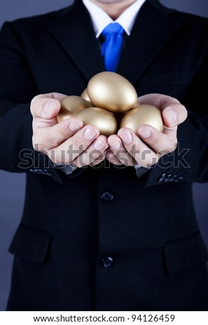 Businessman holding a golden eggs - investment concept - stock photo