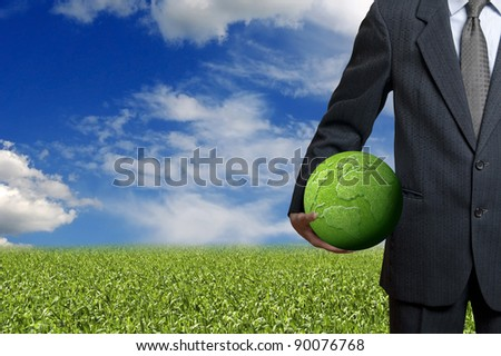 businessman holding a green earth - stock photo