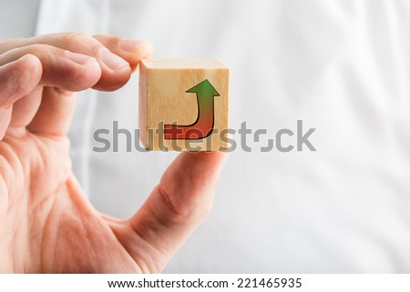 Businessman holding a hand-drawn curving arrow on a wooden block graduating from a red baseline to green at the point showing the route to success.