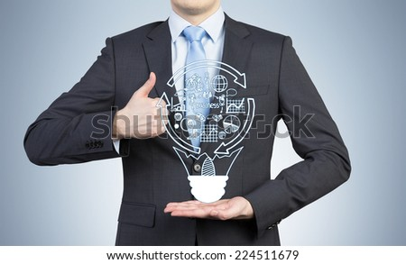 Businessman holding a hologram of business flowchart.