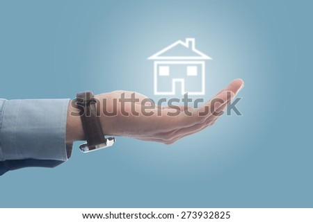 Businessman holding a house in his hand - stock photo