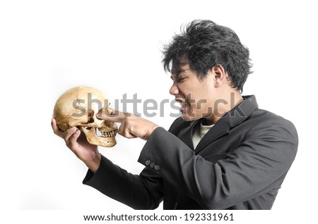 Businessman holding a human skull in hand.