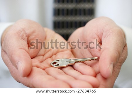 Businessman holding a key in the palm of his hand - stock photo