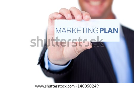 Businessman holding a label with marketing plan written on it on white background - stock photo
