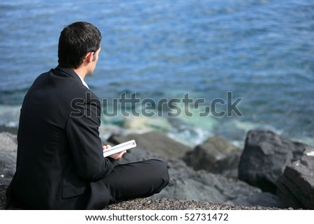 Businessman holding a laptop computer in front of the sea