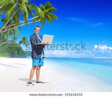 Businessman holding a laptop on a beach. - stock photo
