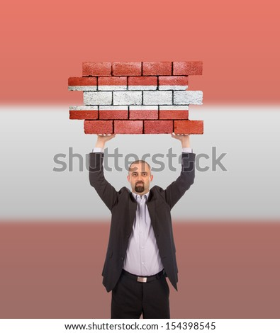 Businessman holding a large piece of a brick wall, flag of Austria, isolated on national flag - stock photo