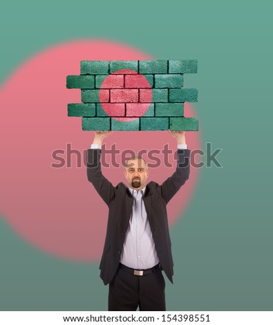 Businessman holding a large piece of a brick wall, flag of Bangladesh, isolated on national flag - stock photo
