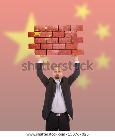 Businessman holding a large piece of a brick wall, flag of China, isolated on national flag - stock photo
