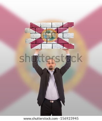 Businessman holding a large piece of a brick wall, flag of Florida, isolated on national flag - stock photo