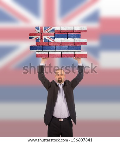 Businessman holding a large piece of a brick wall, flag of Hawaii, isolated on national flag - stock photo