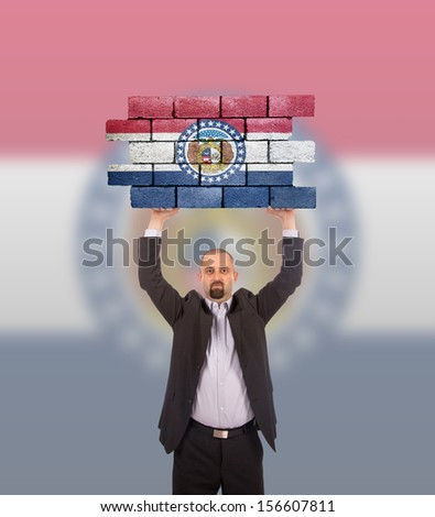 Businessman holding a large piece of a brick wall, flag of Missouri, isolated on national flag - stock photo